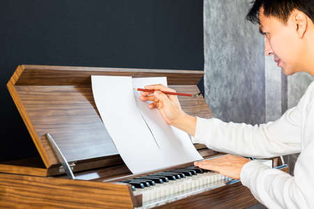 asian male songwriter writing a hit song while playing piano. songwriting concept