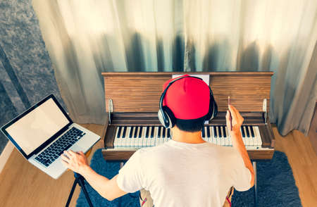 Back of asian male music lover enjoy learning music lesson online from internet in living room. Stock fotó - 164228374