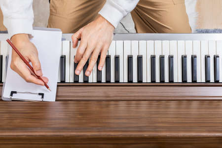 Top view of male songwriter hands writing a hit song on piano.