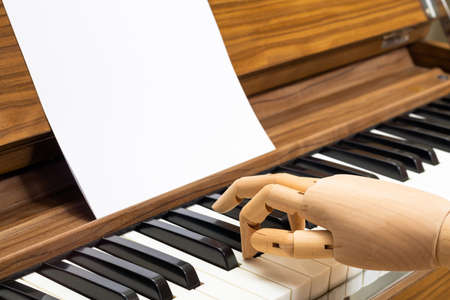 wooden hand model playing on piano keys. improved piano playing that stiff like robot to naturally playing concept