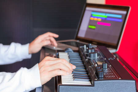 male music composer hands playing synthesizer keyboard for recording midi tracks on laptop computer. music production technology concept