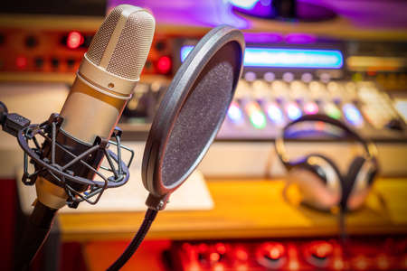 condenser microphone on broadcasting studio equipment background