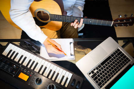 top view of male songwriter writing a song with laptop computer and keyboard on desk. songwriting concept