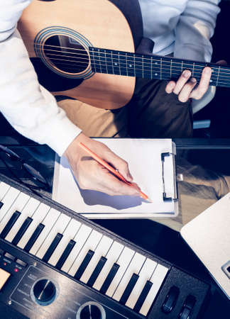 male songwriter writing a song with laptop computer and keyboard on desk. songwriting concept Stock fotó