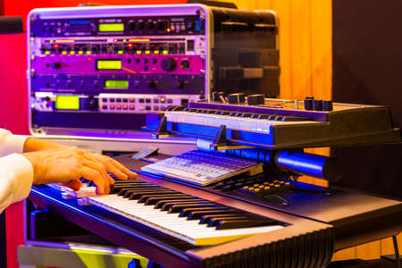 musician hands playing electric piano with soundmodule background in recording studio