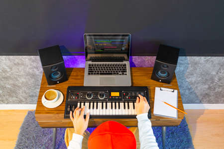 top view of male musician, composer, songwriter arranging music on keyboard synthesizer and computer on desk in home studio. music production technology concept