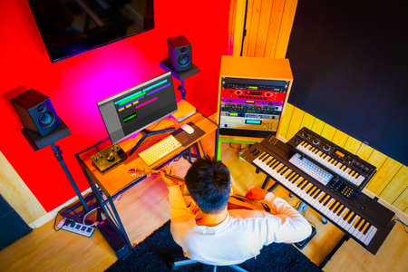 top view of asian male musician recording guitar track in home studio