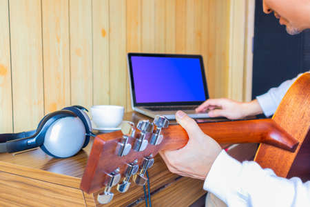 man enjoy learning online guitar lesson from internet in living room. music background Foto de archivo
