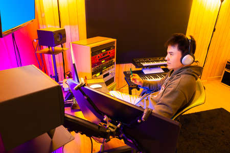 asian male DJ, producer working in broadcasting, recording studio