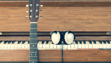 acoustic guitar with headphone on old piano background