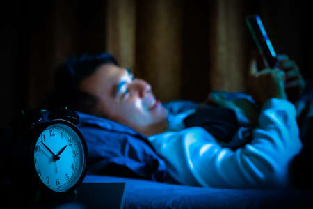 A man playing social media on smartphone in bed at night causing sleep disorder
