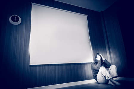 depressed man sitting on floor and holding temple with his hand in dark room