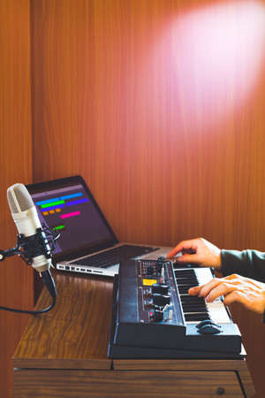 male composer hands playing keyboard synthesizer for recording midi tracks on laptop computer in home studio. music production technology Foto de archivo