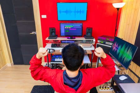 back of asian music producer feel happy when finished his work in recording studio
