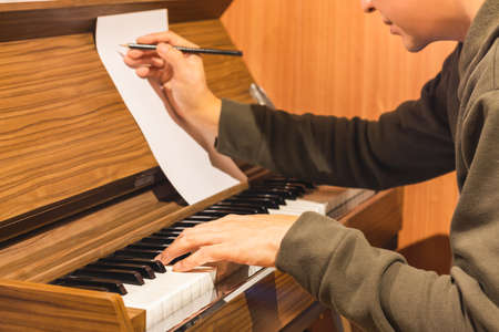 male composer playing piano and writing a song on music sheet