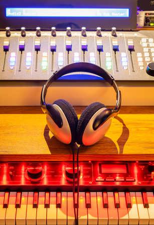 headphone, sound mixer, synthesizer on studio desk