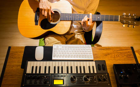 man playing acoustic guitar while learning music lesson from internet. e-learning concept