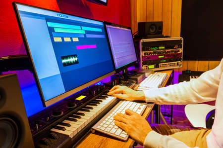 producer, arranger, composer hands playing keyboard for recording midi track on digital audio workstation computer in recording studio. music production concept
