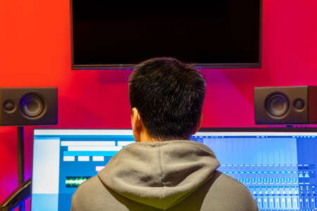back of asian music producer, sound engineer listening audio from monitor speakers