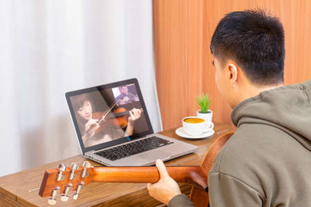 back of young asian male musician jamming music on video call with his friend in living room