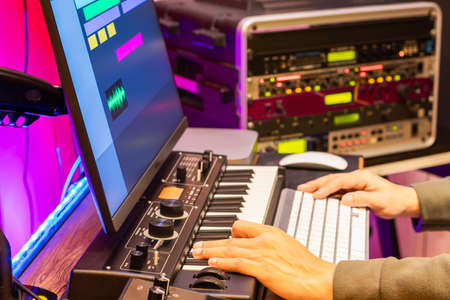 male composer, producer, arranger, song writer, musician hands arranging music on computer in home studio. music production concept Foto de archivo