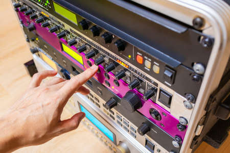 hand tuning knobs of studio gears, pre-amp, audio interface, effect signal processor. TV radio broadcasting, post production or music concept