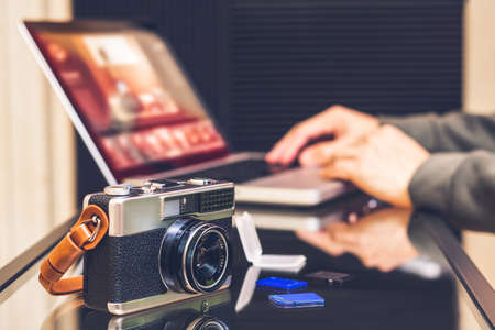 male photographer editing photo on laptop computer, focus on camera on desk