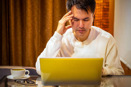 headache, tense young asian man working on laptop computer in bedroom at night Stock fotó