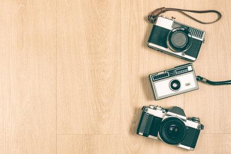 SLR camera, rangefinder camera and compact camera on wooden floor