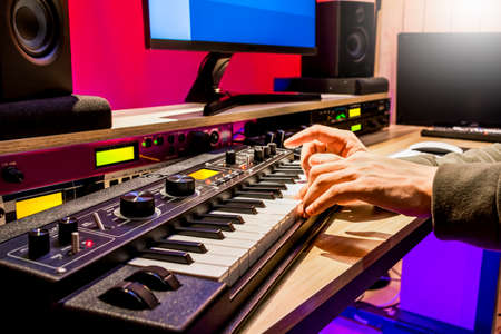male musician hands playing keyboard for recording midi tracks in home studio. music production concept Stock fotó