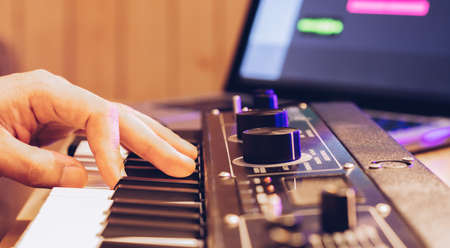 male musician hand playing midi keyboard for arranging music on laptop computer. music production technology concept