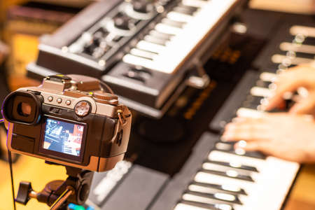 music vlogger streaming a live video while playing piano in home studio Stock fotó