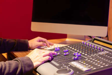 sound engineer hands mixing sound on control surface mixer for recording or live broadcasting in studio