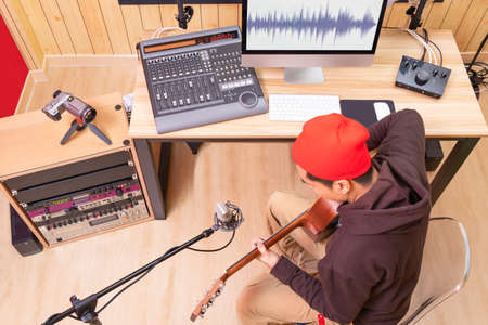music vlogger streaming a live video while playing acoustic guitar in home studio Stock fotó
