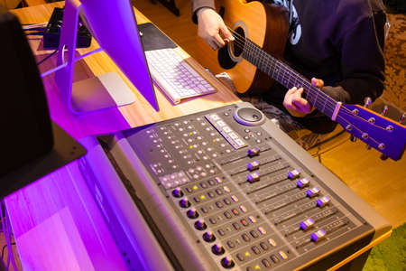 male musician playing acoustic guitar for recording on computer in home studio. music production concept Stock fotó