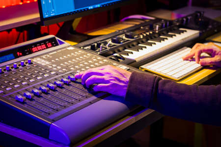close up male sound engineer hand mixing music on digital audio mixing board in sound studio. music production concept Stock fotó