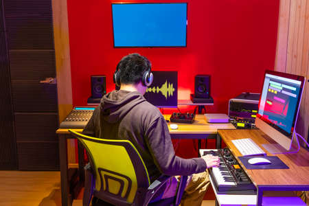 male asian music producer arranging a song on midi keyboard and computer in home recording studio