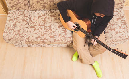 top view of asian male musician playing acoustic guitar in minimalist style living room