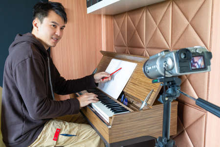 asian young handsome music instructor streaming a live video while teaching his student at home. e-learning technology concept