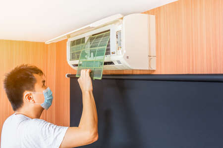 asian man remove dust filter for cleaning air conditioner system