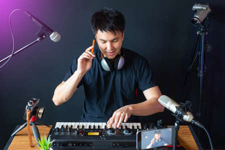 asian young handsome music instructor streaming a live video while teaching his student at home. e-learning technology and work from home concept