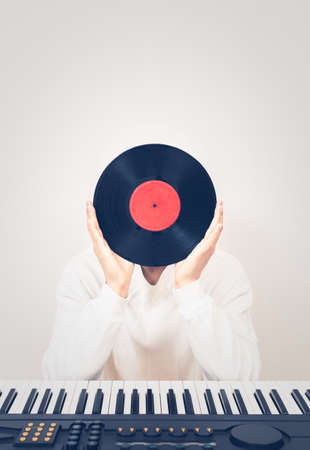 man holding record with electric piano on desk. music background