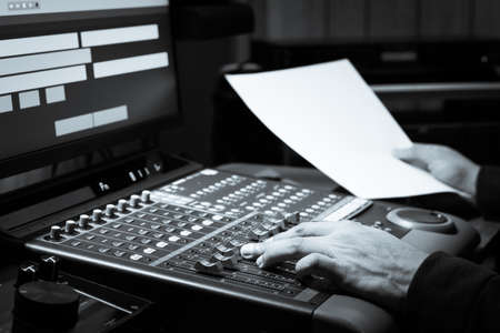 sound engineer hands adjusting volume on audio mixing board in broadcasting, post production studio
