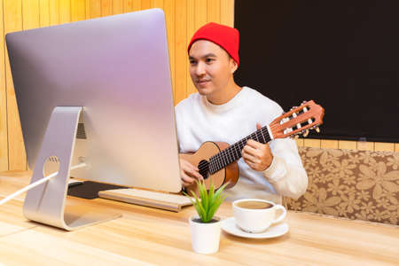 sian handsome man enjoy learning guitar lesson on internet in living room. e-learning technology concept