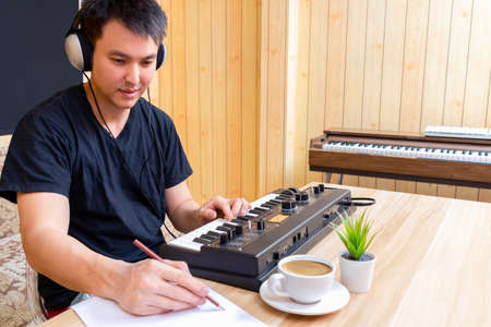 asian handsome male songwriter enjoy writing a hit song while playing music keyboard in living room. songwriting concept