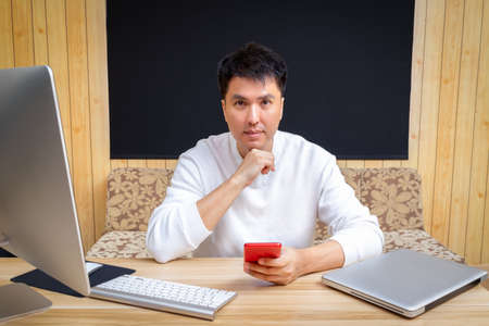 asian handsome man using smartphone and smiling while working from home
