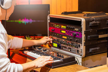 male professional musician playing synthesizer keyboard while editing tone on effect processor equipment in studio. sound design concept