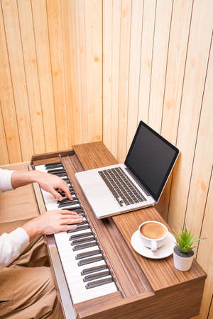 man enjoy learning music lesson online from internet in living room. e-learning technology concept Stock fotó