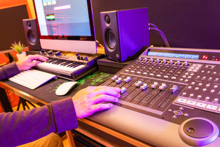 male music producer, sound engineer hands mixing a song on digital control surface mixer in home studio. music production technology
