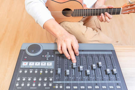 male musician hands adjusting control surface mixing console fader for recording acoustic guitar track on computer